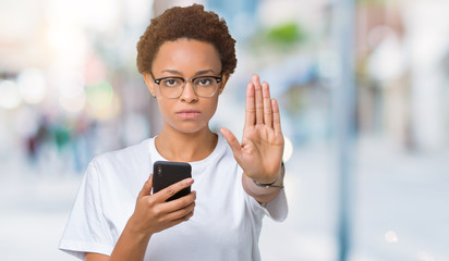 Young african american woman using smartphone over isolated background with open hand doing stop sign with serious and confident expression, defense gesture