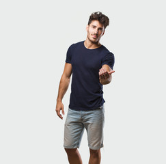 Young handsome man standing inviting to come, confident and smiling making a gesture with hand, being positive and friendly