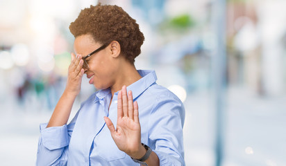 Young beautiful african american business woman over isolated background covering eyes with hands and doing stop gesture with sad and fear expression. Embarrassed and negative concept.
