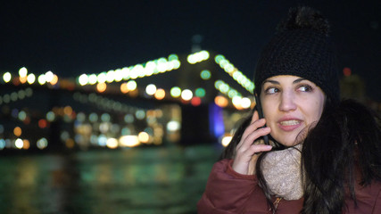 Young woman takes a phone call at Brooklyn Bridge by night