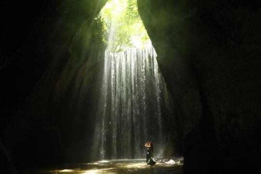 Model in green dress praying in Tukad Cepung waterfall, Bali, Indonesia