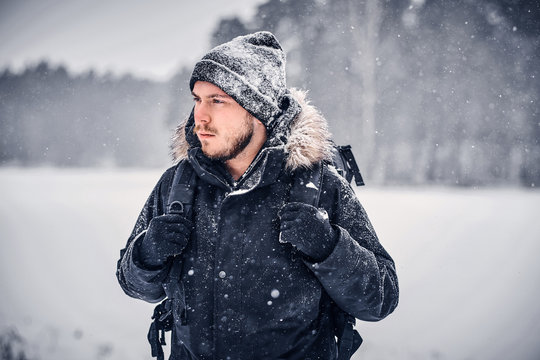 Portrait of a serious hiker guy with a backpack walking through a winter forest