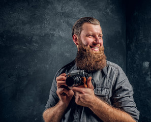 A cheerful bearded photographer wearing a gray holding a photo camera and looking at a camera. Studio shot on a gray textured wall