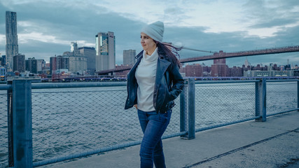 Young woman walks along the wonderful skyline of Manhattan in the evening
