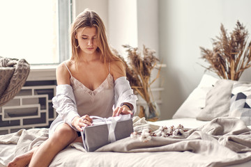 beautiful young blond woman wakes up and finds on the bed at home