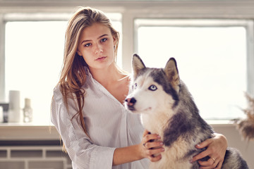 blonde girl playing with her dog husky at home.