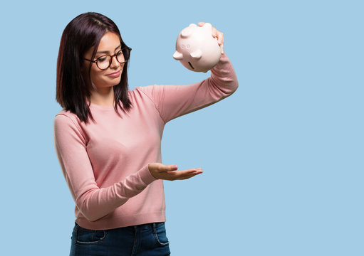 Young pretty woman sad and disappointed, holding a piglet bank, no money left, trying to get something out, face of anger and anguish, concept of poverty