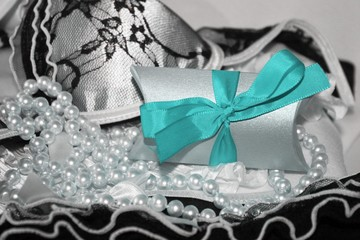 Little gift box with cyan blue ribbon and black and white lacy lingerie background