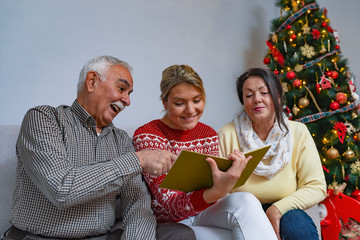 Happy family is reviewing photo album on Christmas. They are sitting on couch and smiling.