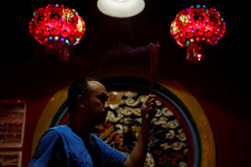 Man carries incense sticks during Chinese Lunar New Year's eve at Dharma Bhakti temple in Jakarta