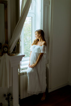 Young pregnant woman standing by the window