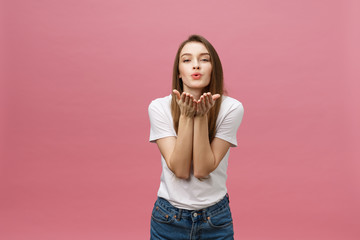 Beautiful woman with makeup and long blonde hair blows kiss, demonstrates her good feelings, says goodbye on distance, isolated over pink background