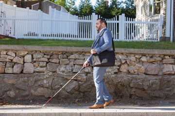 Businessman with visual impairment outside with his cane