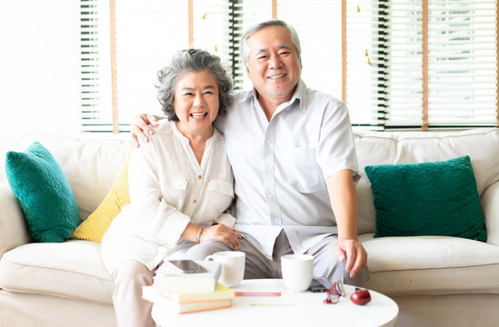 Portrait of a Happy Asian Senior couple relaxing at home on the sofa with the wife hugging her husband  both smiling at camera