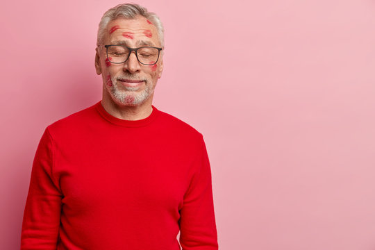Horizontal shot of matured man feels enjoyment and pleasure after recieving kiss from lover, wears spectacles and red jumper, has prints of lipstick on face, models over rosy studio wall, blank space