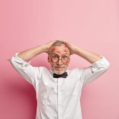 Vertical shot of funny bearded senior male model keeps both hands on head, wears white shirt and round spectacles, poses over rosy background, has kiss marks on face, being in love with colleague