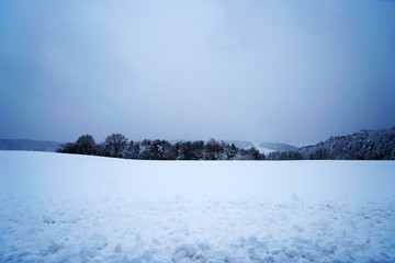 Winter landscape pictures with a lot of snow in cloudy weather in Germany Bavaria included