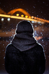 silhouette of a man on the background of falling snow in winter