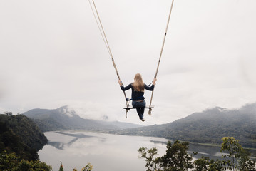 girl on a swing flies over a valley with lakes