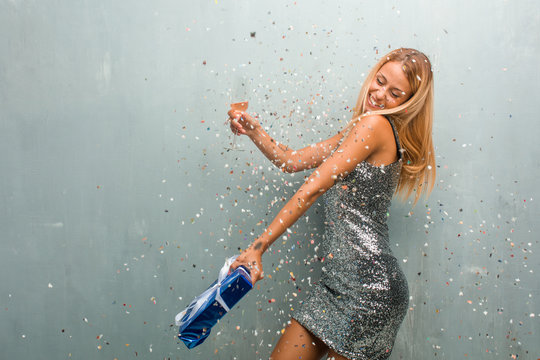 Elegant young blonde woman celebrating new year with champagne, one gift and confetti.