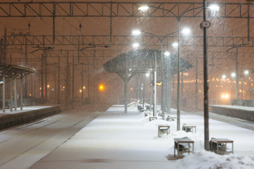 Empty railway platform without passengers in blizzard/heavy snowfall at night. Railway, bad weather concept