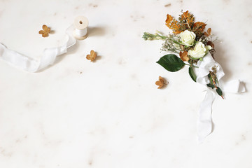 Feminine winter wedding, birthday still life scene. Silk ribbon and bouquet of dry maple leaves, hydrangea, white roses and gypsophila flowers. Marble stone table background. Flat lay, top view.