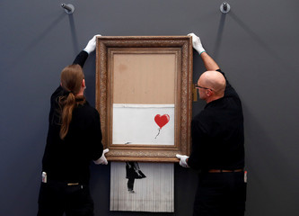 "Employees of the Frieden Burda museum put Banksy's partially shredded artwork ""Love is in the bin"" in place at the museum in Baden Baden"