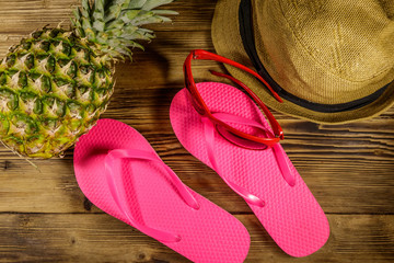 Summer holiday concept. Pineapple, straw hat, flip flops and sunglasses on wooden background