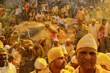 Devotees daubed in turmeric powder watch a procession at shepherd god Khandoba's temple during 'Somvati Amavasya' in Jejuri