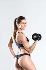 Portrait of a beautiful strong woman with dumbbells on a gray background.