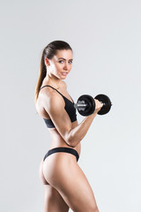 Beautiful sporty woman with dumbbells.