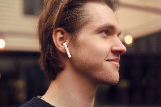 Man in wireless headphones outdoor, street, restaurant. Man listening to e-book, the guy is listening to music. A man in bluetooth headphones is enjoying life.
