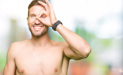 Handsome shirtless man showing nude chest doing ok gesture with hand smiling, eye looking through fingers with happy face.