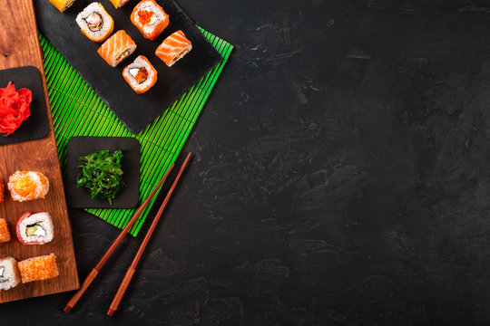 Sushi set with wasabi and ginger on black stone tray on black table. Top view