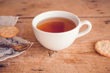 Tee in weißer Tasse auf Holztisch mit Geschirrtuch und kupferfarbenen Löffel