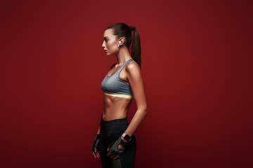 No Pain. No Gain. Sportswoman standing over red background, looking away