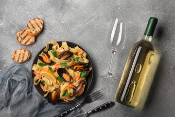 Pasta with seafood and white wine on stone table. Mussels and prawns. Top view.