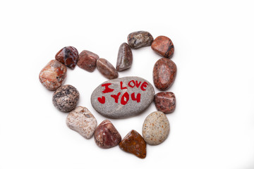 A heart shape image made with pebbles with a pebble with I LOVE YOU painted on it in the center