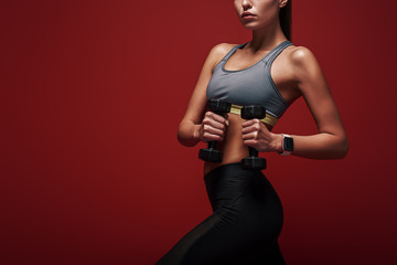 Exercise your mind and body. Sportswoman holds dumbbells standing over red background