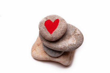 A pile of pebbles with a heart shape painted on the top one