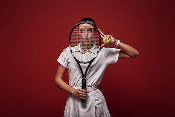Refuse to Lose! Young tennis player standing isolated over red background with a racket and a ball