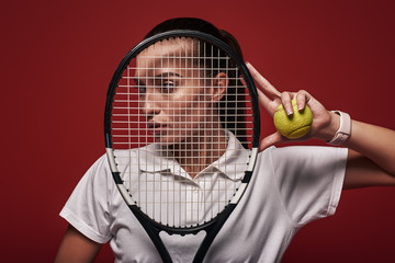 Believe & Achieve. Young tennis player standing isolated over red background with a racket and a ball