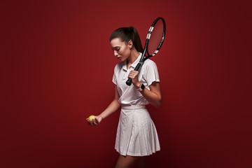 Tennis Anyone? Young tennis player standing isolated over red background with a racket and a ball