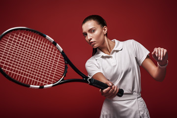 Game, Set, Match! Young tennis player standing isolated over red background with a racket and a ball