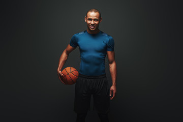 He is a new champion. Handsome sportsman standing over dark background with basketball ball in his hand Wall mural