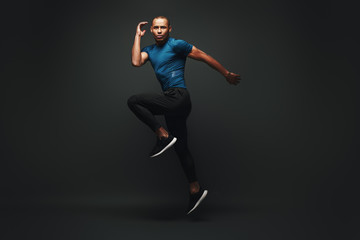 Pushing hard to win. Sportsman jumping over dark background