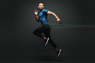 I can do it. Sportsman jumping with resistance band over dark background, looking away