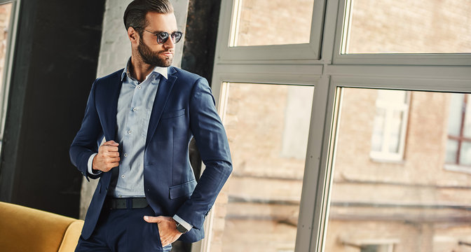 Confident and stylish. Businessman in sunglasses and fashion suit is thoughtfully looking in window while standing at office