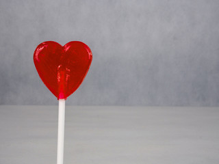 Red, heart-shaped lollypop.