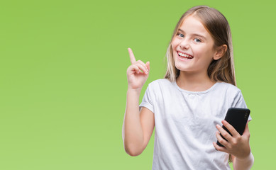 Young beautiful girl sending message texting using smarpthone over isolated background very happy pointing with hand and finger to the side